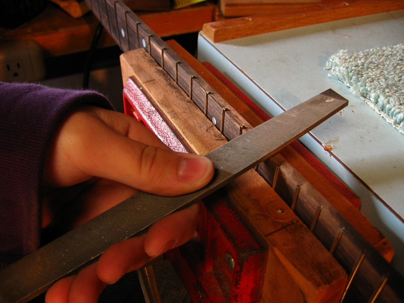 Filing the frets even with the fingerboard.