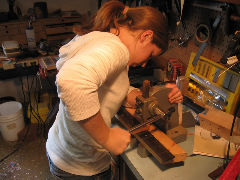Installing the frets using a press.