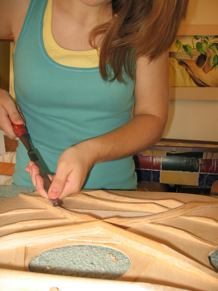 Finish carving the top braces. Carving thins the braces and allows the top to vibrate more freely.
