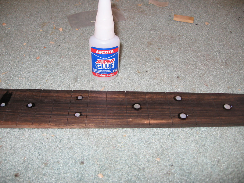 Gluing the position dots in the neck.