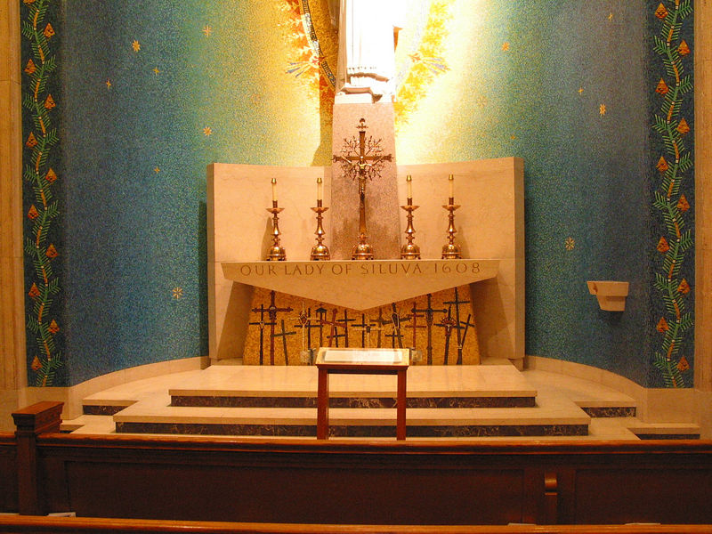 "This is the chapel for Our Lady of Siluva. ""Siluva"" is Lithuanian for ""pine cone,"" explaining the border motif. The crosses beneath the altar are a small version of a famous hill in Lithuania commemorating those killed under Communist rule."