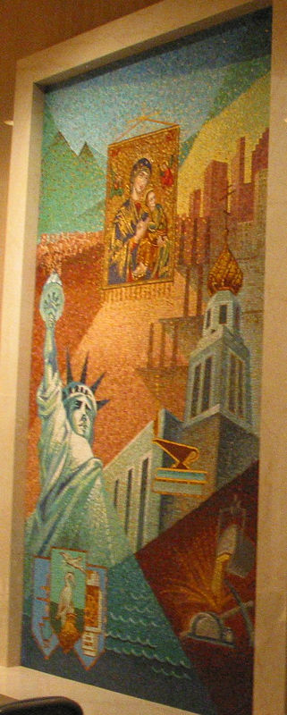 A side mural in the Ruthenian Rite chapel. The icon in the middle is Our Lady of Perpetual Help; the Statue of Liberty is in gratitude for religious freedom; the steel mill is because many immigrants worked in the PA steel mills; and the onion-dome building is the Ruthenian seminary in Pittsburg.
