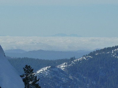 View west from Dewey Point in Yosemite.  This is a zoom-in on two peaks sticking up on the Coast Range.  I believe they are Mt Isabel and Mt. Hamilton, above San Jose.  112 miles away. See this Dewey Point topic.