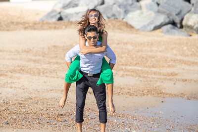 Piggy back on the beach with the bride and groom