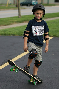 Spencer Warner, age 8, celebrates his birthday with protective gear and new skateboard in an empty parking lot on park Place in Elyria on Sunday. photo by Ray Riedel
