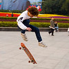 The photographer attempts a kickflip. Apparently Deng Xiaoping likes skateboarding.
