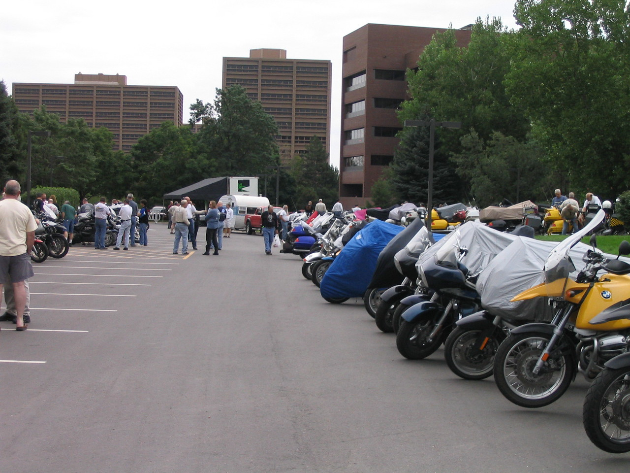 At the end of this row of motorcycles parks a vintage travel trailer.  HUH?