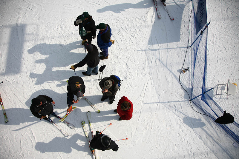 Coaches and skiers gather at the end of a slip run in the morning.