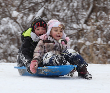 Kylee Weese, age 6, in front, and her older brother Nolan Weese, age 8, both of Elyria get started again down Cascade Park Hill. photo by Ray Riedel