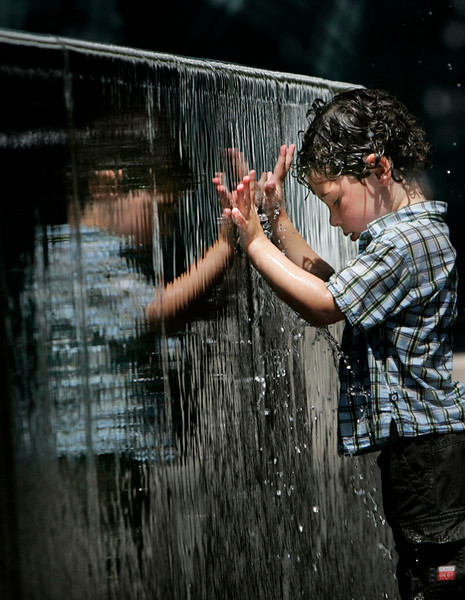 Ethan Eisler visitng his father from Canada, plays with his reflection as he cools off in the water fountains at the City Walk in Universal City.