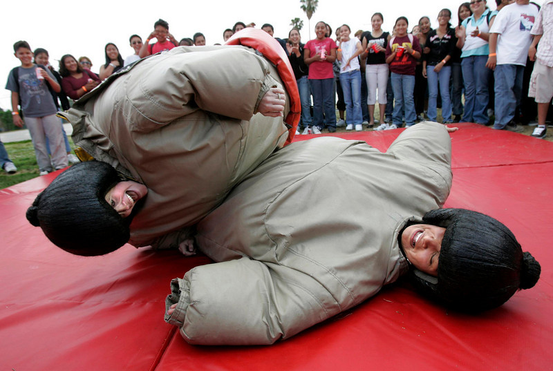 FLOORED:   From left- Vice Principal, Rebecca Speh and Principal, Leticia Zaragoza, sumo wrestle at De Anza Middle School in Ontario at a party that was a reward for students who had perfect attendance for the school year.