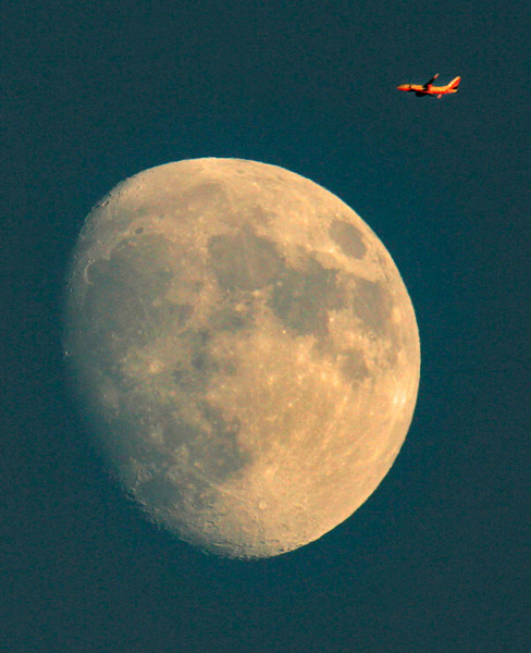 A commercial jet  flies over the moon at sunset over the city of Commerce.