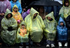 RAIN ON:  Rain cannot dampen the spirit of spectators at the 117th Rose Parade in Pasadena.  The crowds donned raincoats, umbrellas, and blankets to keep warm from the torrential rain that hit the city.