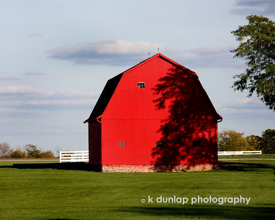 "10.14.09 = Dancing shadows.  I loved how the shadows of the leaves danced on the side of this bright red barn.  Bright blue skies, red barns, green grass and white fences.....perfect comp for photo don't you think?  Sorry I've missed posting for a few days but I've been out of town and running like a mad woman.  Is it Friday yet? <br /> <br /> ""Keep your face toward the sunshine and shadows will fall behind you.""  Walt Whitman"