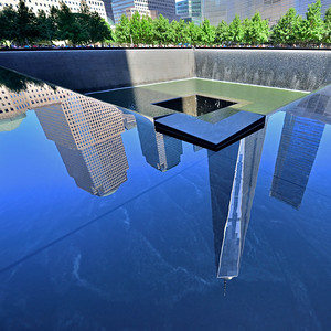 The Freedom Tower and adjacent buildings reflected in the water of the north memorial pool.