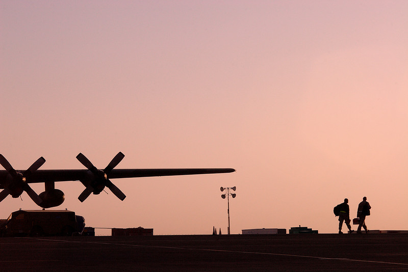 Maintenance troops walk across the flight line as the sun rises; Southwest Asia.