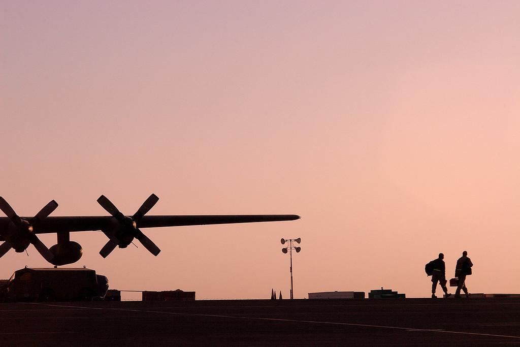 Maintenance troops walk across the flight line as the sun rises; Southwest Asia.