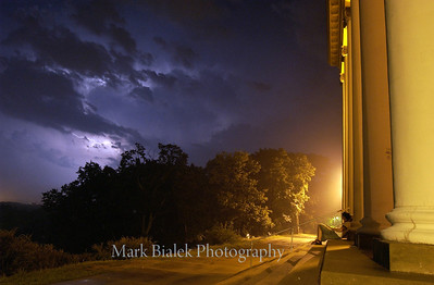 A Western Michigan University student watches an early morning lightning storm on the back steps of the historic East Hall on WMU's East Campus in Kalamazoo.
