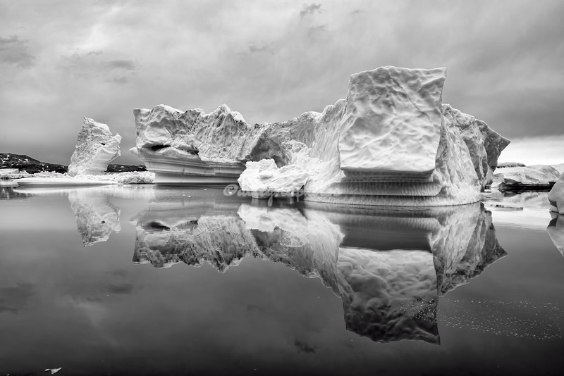 Black and white image of an iceberg and its mirror image, Greenland