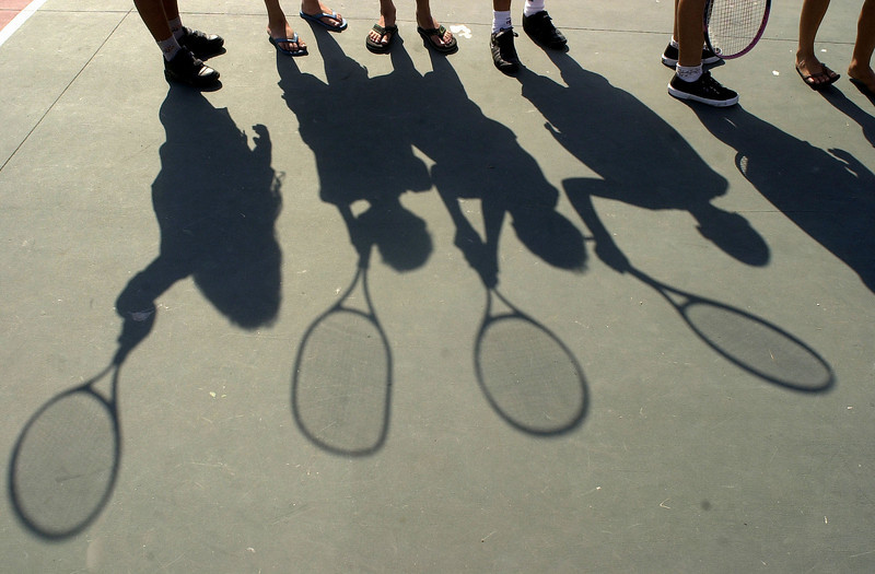 "ADV -- Children taking tennis lessons cast shadows on the court in the Mare slum complex in Rio de Janeiro, Brazil, Thursday, September 6, 2001. Organizers at the community sports complex were surprised at the turnout for tennis, a traditionally elite sport. The poplarity of number one tennis star Gustavo Kuerten, ""Guga"" and the recent failures of the Brazilian soccer team have helped tennis grow in the soccer-mad nation.(AP Photo/Douglas Engle) BRAZIL OUT"