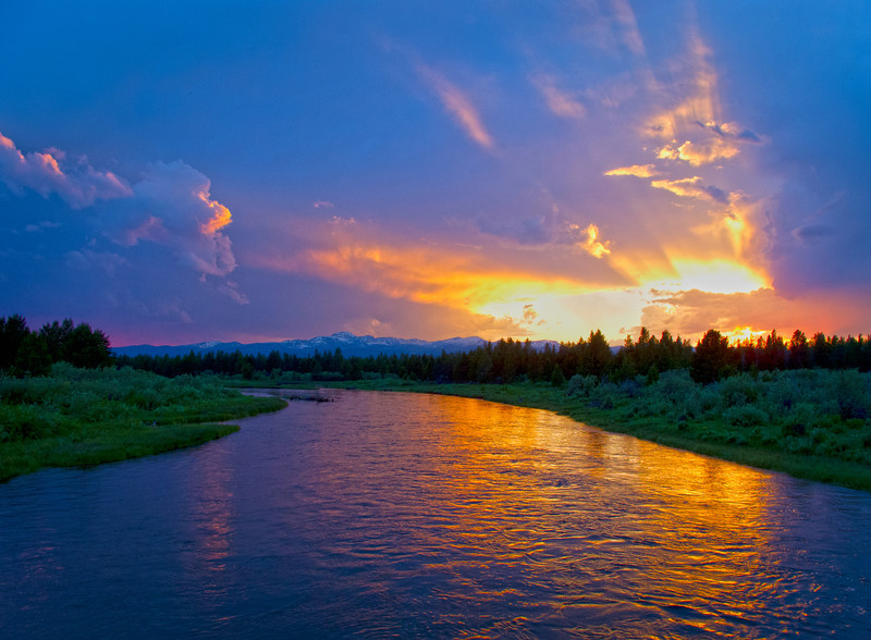 The sun sets amid summer storm clouds over the Madison River near West Yellowstone, MT