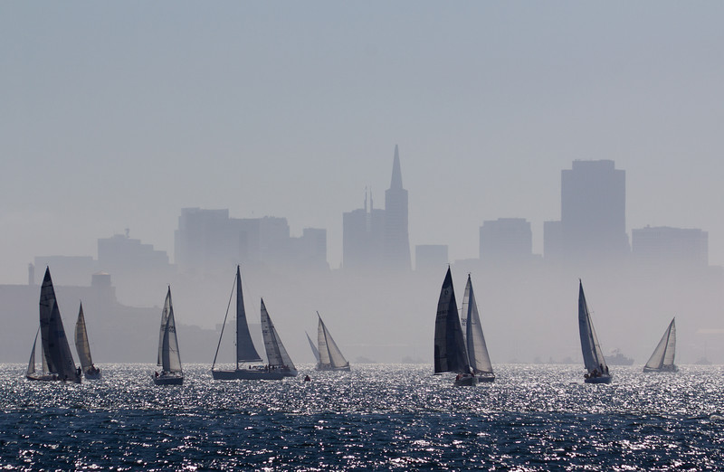 Sailboats ply the choppy waters of San Francisco Bay as an afternoon ocean haze partially obscures the city skyline.