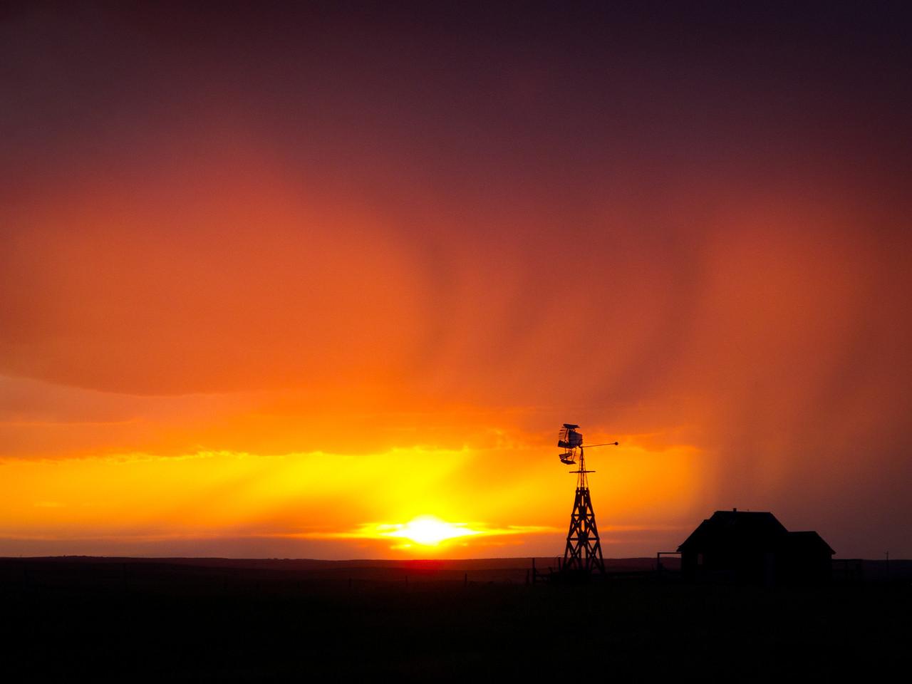 An evening storm passes as the sun sets on the South Dakota prairie.