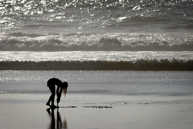 A young girl is silhouetted by the afternoon surf as she draws in the sand on the beach north of Bodega Bay, CA.