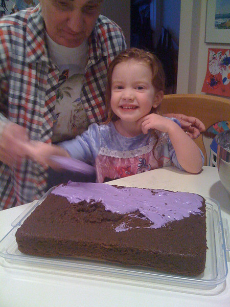 Grandma helping Keira frost her birthday cake