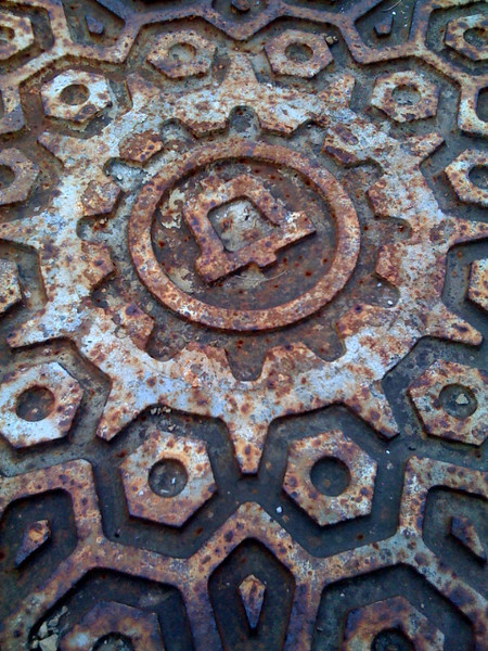 During my walk around campus at work, I often pass by this rusted manhole cover. I always like to take pictures of it, so here's my iPhone version. :)