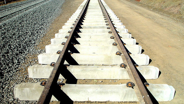 This is the rail line of the future. The bed is super compacted, often with some cement powder in the mix which resists moisture so much better. The sleepers are not affected by weather and no dog spikes to work loose. Soon the ballast will be added and compacted to hold the whole unit in place i hot or cold weather (expansion & contraction). I have heard that the line from Alice Springs to Darwin, if not for the ballast holding it in place on hot days, would expand up to two kms out into the ocean from the unloading port.