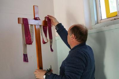 Fr. Angel adjusts the cross.