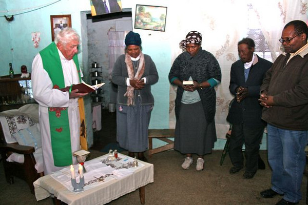 Bishop Joe celebrating a home mass near Middelburg. A picture of Nelson Mandela hangs above the doorway.