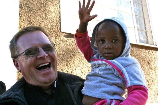 Fr. Peter with one of the mission's youngest soccer fans.