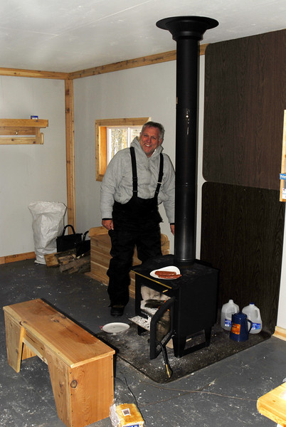 Dan getting the fire going in the little cabin (note the venison dogs)