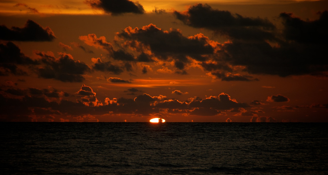The last bits of the sun set behind the clouds on the horizon on Sanibel Island