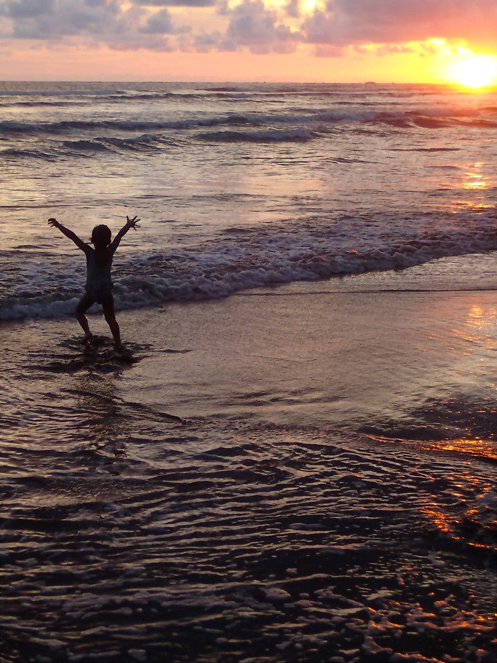 Girl playing on the beach as the sun sets over the Pacific, New Year's day, 2013.  Uvita, Costa Rica.