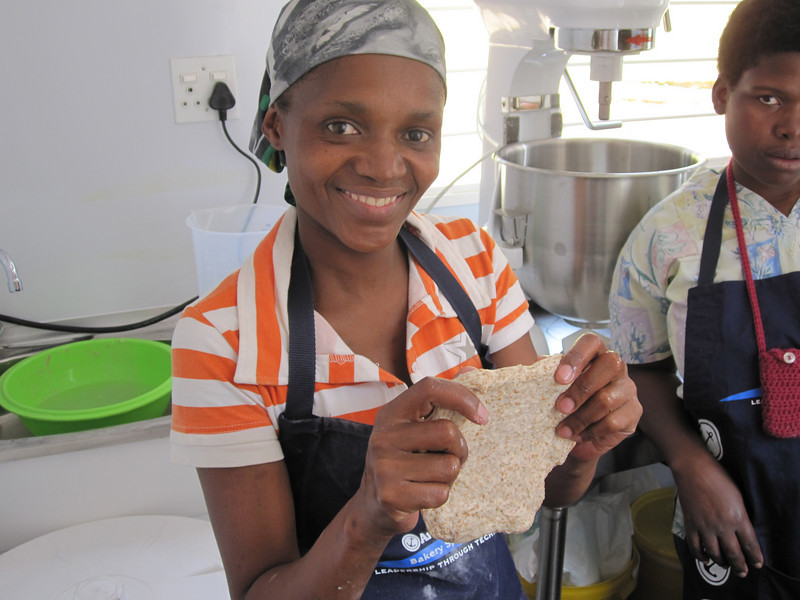 One of the bakers, testing to see the strength of the dough, an apprentice looks on.