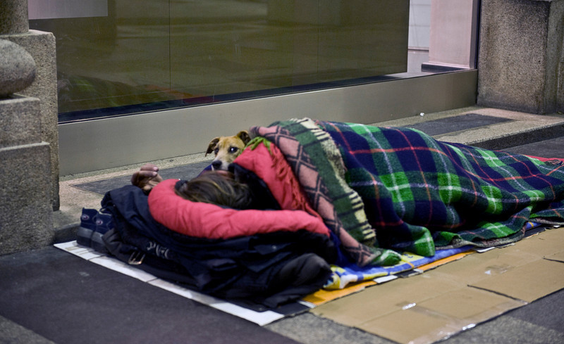 Sleeping rough, with dog, Milan, Italy.
