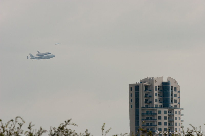 Space Shuttle Endeavour and escort plane fly past the Endeavour Tower High-rise Apartments on Clear Lake.