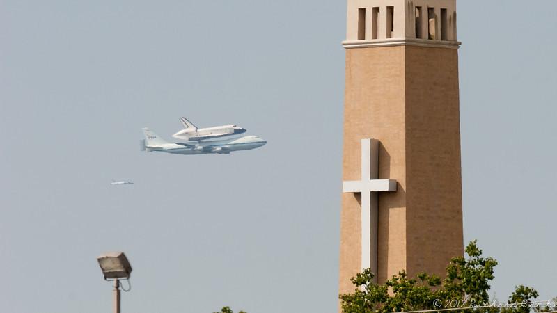 Endeavour passes behind the Christus St. John Hospital Tower.