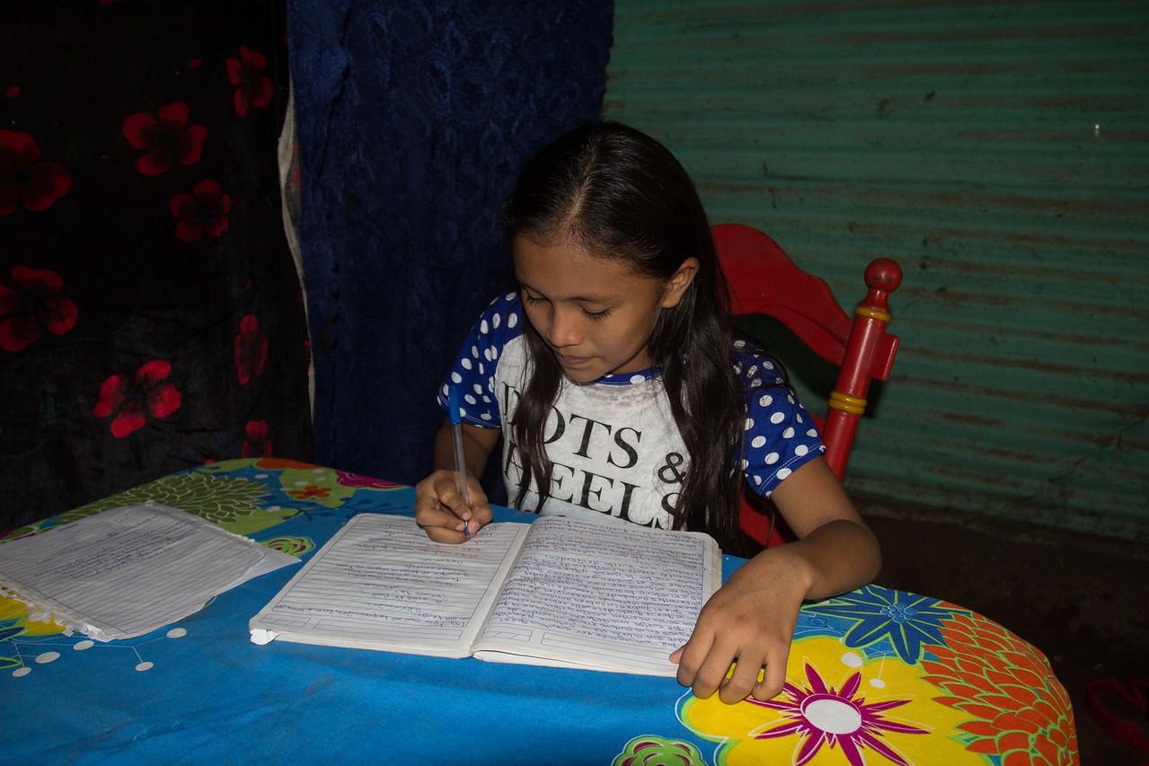 She is doing her homework in house