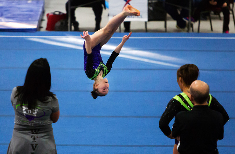 OLD TOWN, Maine -- 03/18/2017 --  A gymnasts tumbles through the air as part of her floor routine during the 2017 Level 6-10 gymnastics state championship at the Old Town-Orono YMCA in Old Town Saturday. Ashley L. Conti | BDN