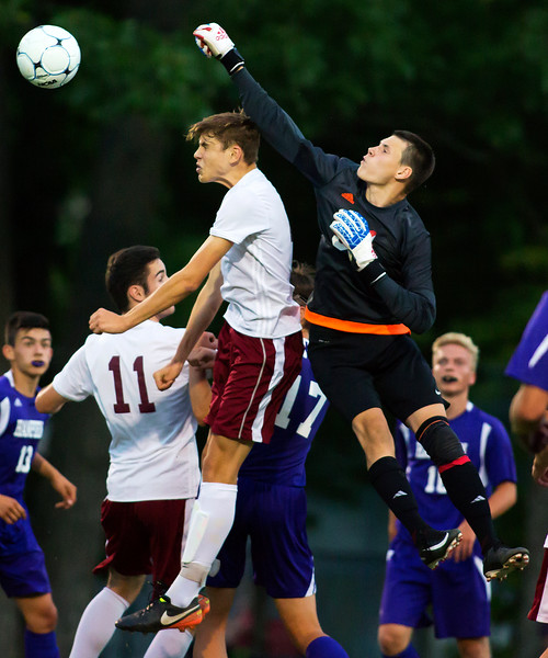 BANGOR, Maine -- 09/12/2017 - Hampden Academy's Sam Lilley (right) punches the ball away from Bangor's Will Hadden during their soccer game at Bangor Tuesday. Ashley L. Conti | BDN