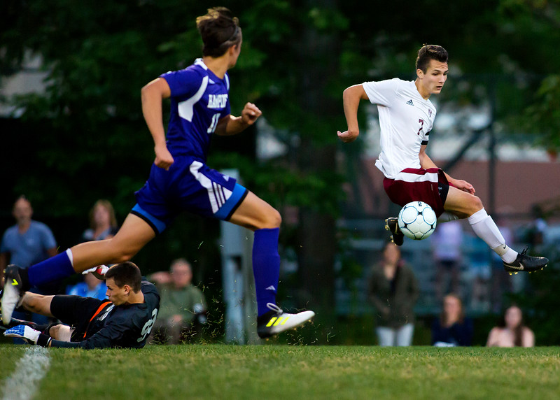 BANGOR, Maine -- 09/12/2017 - Bangor's Garth Berenyi (right) beats Hampden Academy goalkeeper Sam Lilley to break away towards goal during their soccer game at Bangor Tuesday. Berenyi was stopped by Hampden's William Drake. Ashley L. Conti | BDN