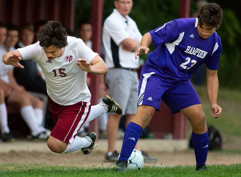 BANGOR, Maine -- 09/12/2017 - Bangor's David Miller (left) gets tripped up while battling for the ball against Hampden Academy's Logan Christian during their soccer game at Bangor Tuesday. Ashley L. Conti | BDN