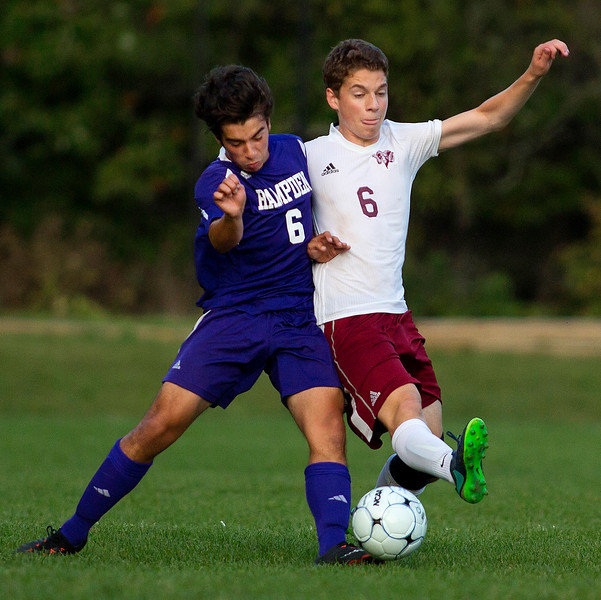BANGOR, Maine -- 09/12/2017 - Hampden Academy's Gavin Partridge (left) and Bangor's Conor O'Brien battle for the ball during their soccer game at Bangor Tuesday. Ashley L. Conti | BDN