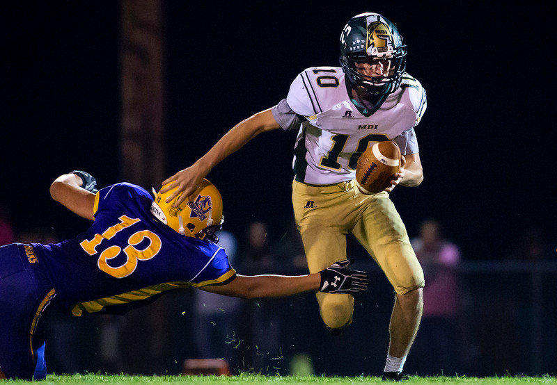 BUCKSPORT, Maine -- 09/15/2017 - Mount Desert Island's Andrew Phelps (right) avoids a tackle attempt by Bucksport's Cameron Soper during their football game at Carmichael Field in Bucksports Friday. Ashley L. Conti | BDN