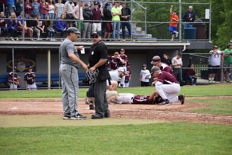 Lisbon baseball coach Randy Ridley (left) discusses a play with home plate umpire Dan Broomhour in the seventh inning of Saturday's Class C state title game at Mansfield Stadium in Bangor. Orono baserunner Kohle Parker (laying on ground) is tended to after being injured in a collision at the plate when he was cut down on an attempted squeeze bunt.