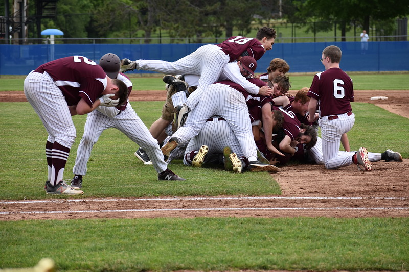 Connor Robertson (left) absorbs the magnitude of the moment while being congratulated by coach Don Joseph (partially obscured) as the Orono High School baseball team celebrates a 4-3 victory over Lisbon for the Class C state championship on Saturday at Mansfield Stadium in Bangor. Orono won 4-3.